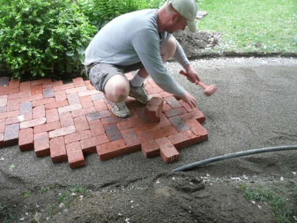 Nate Laying A Herringbone Pattern Of Clay Pavers